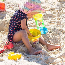Girl playing with sand on a sand pit