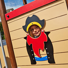 Boy on a pirate themed multi play structure