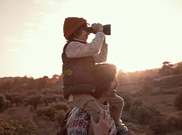 child looking through binoculars on dad's shoulders