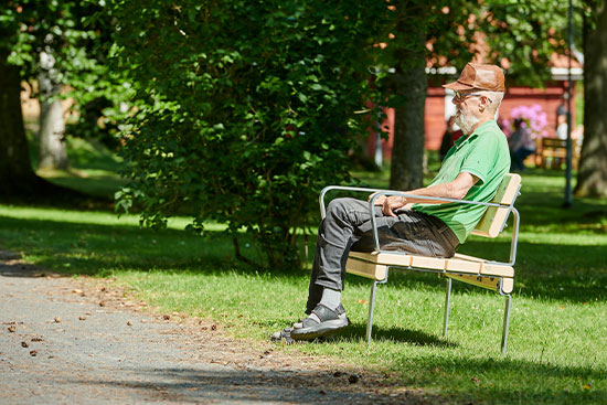 man sitting on park bench with back and arm rests