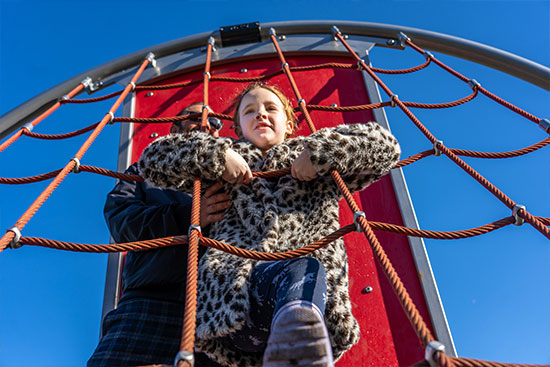child climbing a net structure in a playground