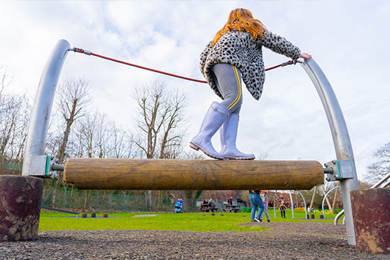 girl walking on a playground rolling beam