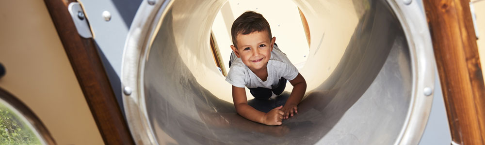 Little boy crawling through a tunnel